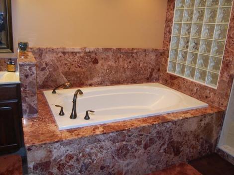 Tub splash skirt and decking in Breccia Paradiso